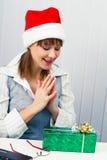 Muchacha en la oficina en los sombreros de Papá Noel con un regalo Foto de archivo