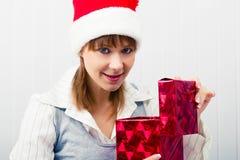 Muchacha en la oficina en los sombreros de Papá Noel con un regalo Fotografía de archivo