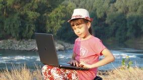 Muchacha en la orilla del río con un ordenador portátil Niña con un ordenador portátil en el banco de un río rápido almacen de metraje de vídeo