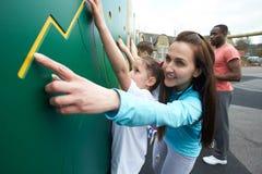 Muchacha en la pared que sube en clase de la educación física de la escuela Foto de archivo libre de regalías
