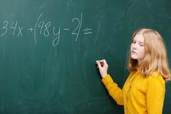 muchacha en la pizarra en una clase de las matemáticas Fotografía de archivo