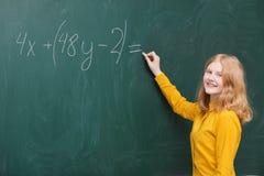 muchacha en la pizarra en una clase de las matemáticas Imagen de archivo libre de regalías