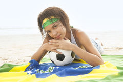 Muchacha en la playa con la bandera y el fútbol del Brasil Fotos de archivo libres de regalías