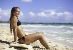 Muchacha en la playa con la tabla hawaiana Imagenes de archivo