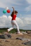 Muchacha en la playa con los globos Imagen de archivo