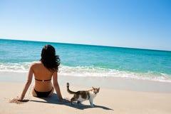 Muchacha en la playa con un gatito Fotos de archivo