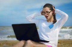 Muchacha en la playa con un ordenador portátil, emociones Imagen de archivo
