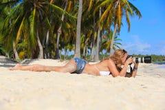 Muchacha en la playa del Caribe con una cámara Fotografía de archivo