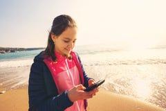Muchacha en la playa del invierno que sostiene un teléfono Imágenes de archivo libres de regalías