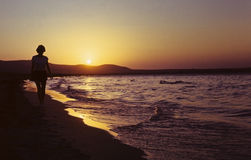 Muchacha en la playa en la salida del sol Imágenes de archivo libres de regalías