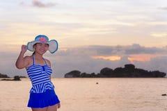 Muchacha en la playa en la salida del sol sobre el mar Fotos de archivo libres de regalías
