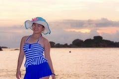 Muchacha en la playa en la salida del sol sobre el mar Imagenes de archivo