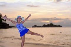 Muchacha en la playa en la salida del sol sobre el mar Fotografía de archivo