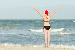 Muchacha en la playa en los sombreros de Papá Noel Manos levantadas para arriba Visión posterior Fotos de archivo