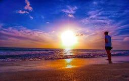 Muchacha en la playa en la puesta del sol Foto de archivo