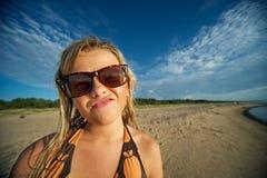 Muchacha en la playa que hace la cara divertida Imagen de archivo
