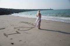Muchacha en la playa que hace a una muchacha del photoblonde en vestido y viento de la playa fotos de archivo libres de regalías