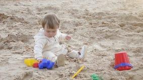 Muchacha en la playa que juega en la arena con los juguetes almacen de video