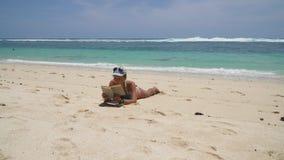 Muchacha en la playa que lee un libro almacen de video