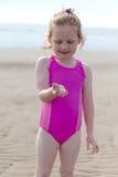 Muchacha (5) en la playa que lleva a cabo la cáscara Fotografía de archivo