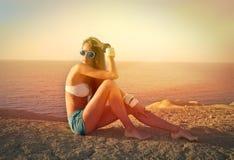 Muchacha en la playa que mira lejos Foto de archivo