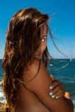Muchacha en la playa que mira a través del pelo con un ojo Foto de archivo