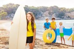 Muchacha en la playa que se coloca con el tablero de resaca Fotografía de archivo