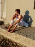 Muchacha en la playa que se sienta en el sol Imagenes de archivo