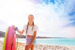 Muchacha en la playa soleada arenosa que dobla sobre cámara Foto de archivo libre de regalías