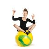 Muchacha en la posición de loto respecto a un globo amarillo grande Foto de archivo libre de regalías