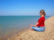 Muchacha en la posición de la yoga respecto a una playa vacía Foto de archivo