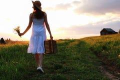 Muchacha en la primavera en el campo Una muchacha con una maleta camina th Foto de archivo libre de regalías