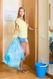 Muchacha en la puerta con los bolsos de basura Foto de archivo libre de regalías