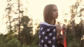 Muchacha en la puesta del sol con la bandera americana en manos metrajes