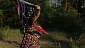 Muchacha en la puesta del sol con la bandera americana en manos almacen de video