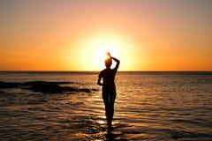 Muchacha en la puesta del sol de oro en la playa imagen de archivo