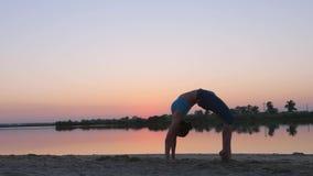 Muchacha en la puesta del sol que muestra ejercicios gimnásticos metrajes