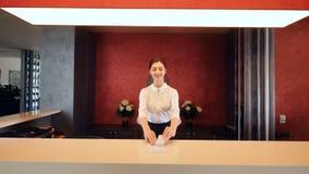 Muchacha en la recepción que sonríe y que da la llave electrónica Pasillo del hotel metrajes