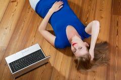Muchacha en la relajación de madera de un suelo y una computadora portátil Imagen de archivo
