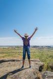 Muchacha en la roca con las manos para arriba Foto de archivo libre de regalías