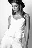 Muchacha en la ropa blanca y el sombrero negro que presentan en estudio en el fondo blanco Foto blanco y negro de Pekín, China Imagenes de archivo