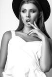 Muchacha en la ropa blanca y el sombrero negro que presentan en estudio en el fondo blanco Foto blanco y negro de Pekín, China Imagen de archivo libre de regalías