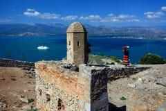 Muchacha en la ropa brillante que toma las fotos del castillo de Palamidi, Nafplio, Grecia fotos de archivo