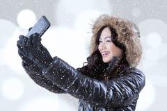 Muchacha en la ropa caliente que toma la imagen del selfie Imagen de archivo libre de regalías