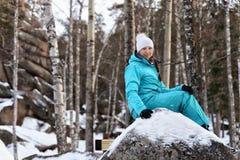 Muchacha en la ropa de deportes azul que se sienta en un canto rodado grande en la naturaleza en el fondo de rocas en el invierno imagen de archivo