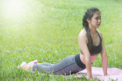 Muchacha en la ropa de deportes verde que hace yoga imagenes de archivo