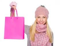 Muchacha en la ropa del invierno que muestra bolsos de compras Imagenes de archivo