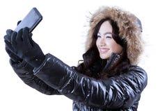 Muchacha en la ropa del invierno que toma la foto del uno mismo Imagen de archivo libre de regalías