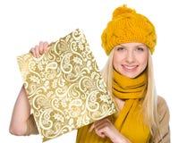 Muchacha en la ropa del otoño que muestra el bolso de compras Fotografía de archivo