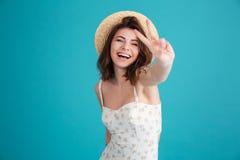 Muchacha en la ropa del verano que muestra gesto de la paz Foto de archivo